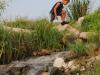 Niño cruzando un arroyo de aguas negras.