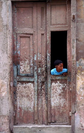 Boy looking out from a door, Havana. Photo by James NG