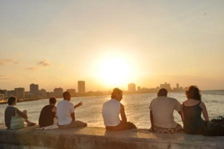 Three American friends sit with three Cuban friends, taking in the sunset together.