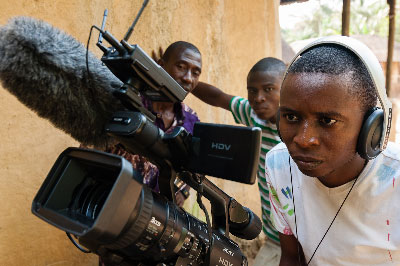 Barmmy checking on the photographic setting before filming. In the back is Joseph (left) and Solomon looking on.